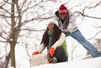 African American couple sledding on snowy hill 11018034247  写真素材・ストックフォト・画像・イラスト素材 アマナイメージズ