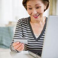 Japanese woman holding credit card using laptop