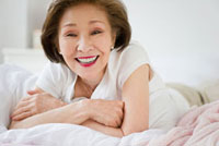 Japanese woman laying in bed smiling