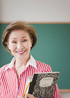 Japanese woman holding books in classroom