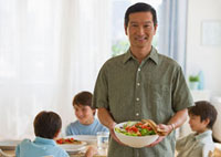 Smiling father holding salad with sons at table in backgroun