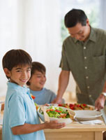 Smiling boy serving salad to family