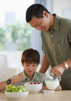 Smiling father pouring milk on son's cereal