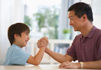 Smiling father and son arm wrestling at table