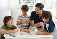 Father and sons playing cards in living room