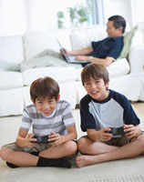 Smiling twin brothers playing video game while father uses l