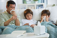 Sick father and sons blowing noses and checking temperature