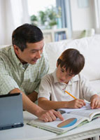 Father helping son with homework in living room