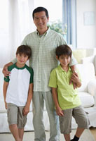 Smiling father and twin sons in living room