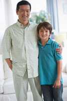 Smiling father and son hugging in living room