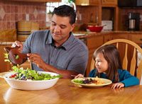 Father serving daughter salad at dinner table