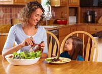 Mother serving daughter salad
