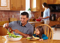 Father serving daughter salad