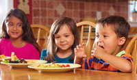 Children eating dinner at table together