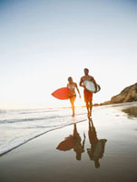 Couple walking on beach carrying surfboards