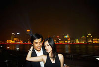 Chinese couple hugging on city waterfront