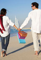 Couple carrying shopping bags walking beach together