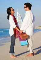 Couple carrying shopping bags standing beach together