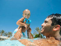 Father swimming in swimming pool with daughter