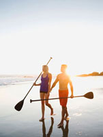Couple walking on beach carrying paddles