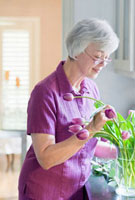 Mixed race woman arranging tulips in vase