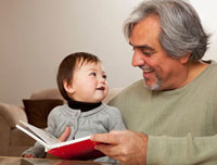 Grandfather reading book to granddaughter
