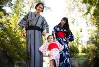 Mixed race family in garden wearing Japanese kimonos