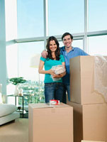 Couple packing cardboard boxes together
