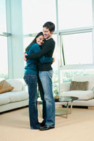 Couple hugging in living room