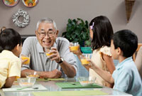 Asian grandfather and grandchildren drinking orange juice