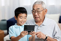 Asian grandfather watching grandson with video game