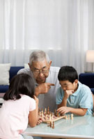 Asian grandfather and grandchildren playing chess