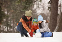 Chinese mother making snowman with children