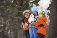 Chinese mother and children holding small snowman
