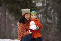 Chinese mother and son holding small snowman