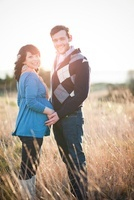 Pregnant woman holding husband's hands in field