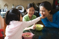 Asian mother and daughters eating breakfast in kitchen 11018037079| 写真素材・ストックフォト・画像・イラスト素材|アマナイメージズ