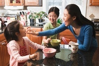 Asian mother and daughters eating breakfast in kitchen 11018037080| 写真素材・ストックフォト・画像・イラスト素材|アマナイメージズ