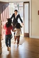 Asian girls greeting mother in doorway