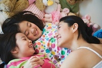 Asian mother laying in bed with daughters