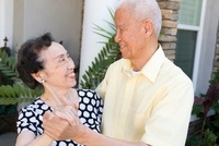 Senior Chinese couple dancing outdoors