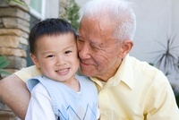 Chinese grandfather hugging grandson