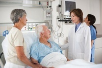 Doctor talking to patient in hospital bed