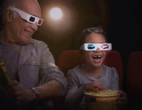 Grandfather and granddaughter watching 3-D movie in theater