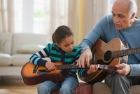 Grandfather teaching granddaughter how to play guitar 11018037867| 写真素材・ストックフォト・画像・イラスト素材|アマナイメージズ