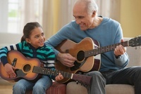 Grandfather teaching granddaughter how to play guitar 11018037868| 写真素材・ストックフォト・画像・イラスト素材|アマナイメージズ