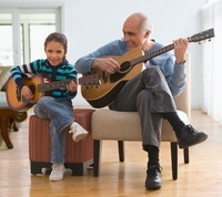 Grandfather teaching granddaughter how to play guitar 11018037869| 写真素材・ストックフォト・画像・イラスト素材|アマナイメージズ