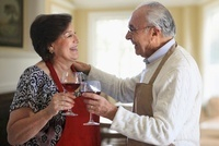 Hispanic couple toasting with red wine