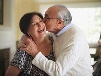 Hispanic man kissing wife on cheek