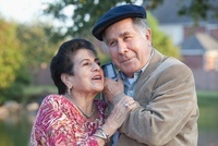 Hispanic couple listening to cell phone together